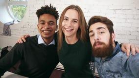 Glimlachend toevallig commercieel team die terwijl het nemen selfies in het bureau stellen Creatief divers commercieel team in mo stock video