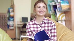 Glimlachend universitair meisje die in lezingsruimte een wetenschappelijk tijdschrift doorbladeren stock footage