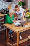 Glimlachend vrijwilligersmeisje dat met wit-haired oma aan leningsontwerp werkt royalty-vrije stock afbeelding