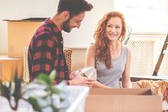 Glimlachend vrouw en man verpakkingsmateriaal tijdens verhuizing aan nieuw huis royalty-vrije stock afbeelding
