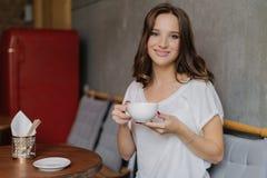 Glimlachend vrouw met tedere glimlach, houdt kop thee of koffie, geniet van goede rust, stelt in comfortabele koffie of het resta royalty-vrije stock afbeeldingen