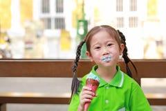 Glimlachend weinig Aziatisch jong geitjemeisje geniet van etend roomijskegel met vlekken rond haar mond stock afbeelding