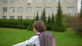Glimlachend weinig student van de jongensschooljongen met rugzak die en aan school in openlucht gaan lopen, Eerstegraads primaire
