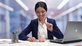 Glimlachend wijfje in businesswear het werpen muntstuk in piggybank, besparingen voor toekomst stock video