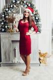 Glimlachend wijfje die in rode santahoed camera en het stellen bekijken royalty-vrije stock fotografie