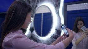 Glimlachend wijfje die selfie foto die op smartphone maken zich voor spiegel in toilet bevinden stock video