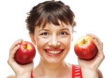 Glimlachend wijfje die twee rode appelen houden stock afbeelding