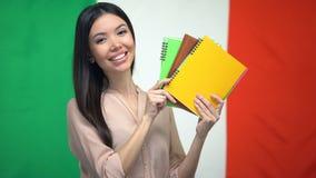 Glimlachend wijfje die voorbeeldenboeken tegen Italiaanse vlag, vreemde taalcursussen tonen stock footage