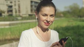Glimlachend wijfje in hoofdtelefoons met smartphone stock video
