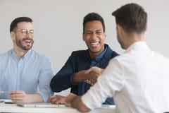 Glimlachend zakenliedenhanddruk worden die die op vergadering #_a op de hoogte brengen royalty-vrije stock afbeelding