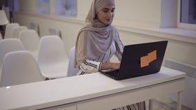 Glimlachend zeker moslimwijfje die een hijabzitting op een witte stoel in de moderne conferentiezaal online dragen met a stock footage