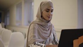 Glimlachend zeker moslimwijfje die een hijabzitting op een witte stoel in de moderne conferentiezaal online dragen met a stock videobeelden