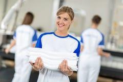 Glimlachende aangewende holding schone en het strijken textiel royalty-vrije stock foto