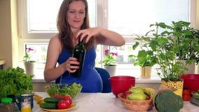 Glimlachende aanstaande moeder die salade van verse organische groenten maken stock videobeelden