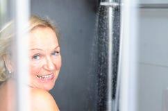 Glimlachende aantrekkelijke hogere vrouw die een douche nemen stock foto's