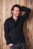 Glimlachende aantrekkelijke jonge mens in zwart overhemd die en het stellen bevinden zich Stock Fotografie