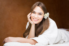 Glimlachende aantrekkelijke jonge vrouw in een witte robe royalty-vrije stock fotografie