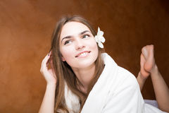 Glimlachende aantrekkelijke jonge vrouw in een witte robe stock afbeelding