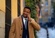 Glimlachende aantrekkelijke modieuze rijpe mens die slimme telefoon in stedelijke in openlucht stad met behulp van royalty-vrije stock afbeelding