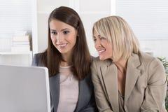 Glimlachende aantrekkelijke onderneemster twee die in een team werken die a kijken Stock Foto