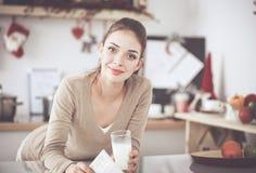 Glimlachende aantrekkelijke vrouw die ontbijt in keukenbinnenland hebben Glimlachende aantrekkelijke vrouw Royalty-vrije Stock Afbeeldingen
