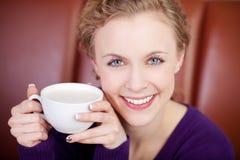 Glimlachende aantrekkelijke vrouw die van kop van koffie genieten Stock Afbeeldingen