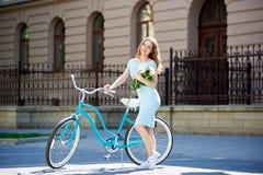 Glimlachende aantrekkelijke vrouwelijke dragende bloemen en het stellen naast blauwe fiets voor het mooie historische buinding stock foto