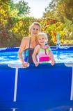 Glimlachende actieve moeder en dochter in zwembad stock fotografie