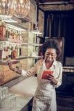 Glimlachende Afrikaans-Amerikaanse barman die nieuw cocktailrecept lezen bij zolderbar royalty-vrije stock afbeelding