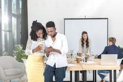 glimlachende Afrikaanse Amerikaanse bedrijfsmensen die smartphone samen gebruiken royalty-vrije stock afbeeldingen