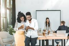 glimlachende Afrikaanse Amerikaanse bedrijfsmensen die smartphone samen gebruiken stock afbeeldingen
