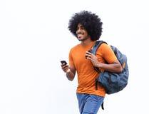 Glimlachende Afrikaanse Amerikaanse mens die met zak en cellphone lopen Royalty-vrije Stock Foto