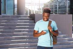 Glimlachende Afrikaanse Amerikaanse student die cellphone bekijken royalty-vrije stock fotografie