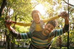 Glimlachende Afrikaanse Amerikaanse vader die zijn dochter op piggyba vervoeren stock afbeelding