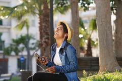 Glimlachende Afrikaanse Amerikaanse vrouw die aan muziek op celtelefoon luisteren Royalty-vrije Stock Afbeeldingen