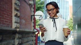 Glimlachende Afrikaanse Amerikaanse vrouw die de koffie gebruiken die van de smartphoneholding in openlucht lopen stock footage