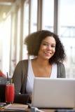 Glimlachende Afrikaanse Amerikaanse vrouw die laptop met behulp van bij koffie Stock Foto