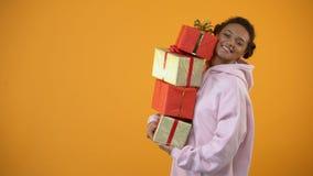 Glimlachende Afrikaanse Amerikaanse vrouw die vele giftboxes houden, die voor vakantie voorbereidingen treffen stock footage