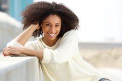 Glimlachende Afrikaanse Amerikaanse vrouw met krullende haarzitting in openlucht Stock Afbeelding