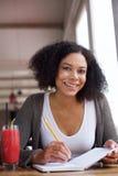 Glimlachende Afrikaanse Amerikaanse vrouwelijke student die in boek schrijven Royalty-vrije Stock Fotografie