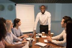 Glimlachende Afrikaanse busleider die camera op teamvergadering bekijken stock foto's