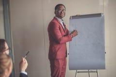 Glimlachende Afrikaanse jonge mens die in glazen businessplan op flipchart schrijven Royalty-vrije Stock Afbeeldingen