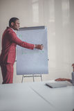Glimlachende Afrikaanse jonge mens die in glazen businessplan op flipchart schrijven Royalty-vrije Stock Fotografie