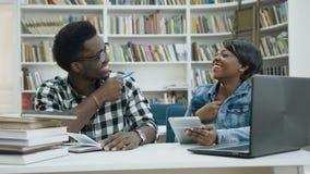 Glimlachende Afrikaanse mannelijke en vrouwelijke studenten die tablet in bibliotheek gebruiken stock footage