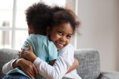 Glimlachende Afrikaanse meisjeszuster die weinig jongensbroer thuis omhelzen royalty-vrije stock afbeelding