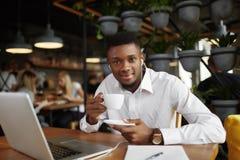 Glimlachende Afrikaanse mens bij koffiepauze in koffie Stock Fotografie