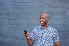 Glimlachende Afrikaanse mens die mobiele telefoon bekijken Stock Foto