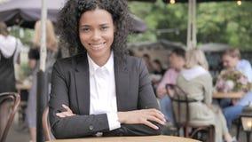 Glimlachende Afrikaanse Onderneemster Sitting in Openluchtkoffie stock footage