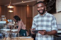 Glimlachende Afrikaanse ondernemer die bij de teller van zijn koffie werken royalty-vrije stock afbeeldingen