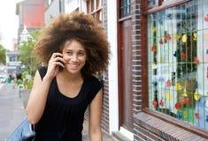 Glimlachende Afrikaanse vrouw die en op celtelefoon lopen spreken Stock Foto